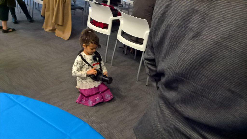 "The TR Anniversary Party is a family affair. Here's my 5-year-old, who gamely snapped a photo of her Dad with Phil Sharp. She was well-behaved, enduring Dad's ""boring, boring, boring"" biotech event."